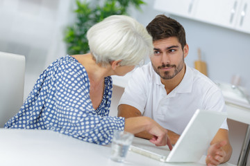 young man explaining to elderly woman how to use laptop