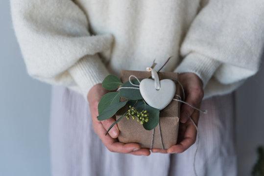 Geschenk wird von Frau schön verpackt und in Händen gehalten