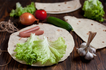 cooking burrito with greens, cucumbers, tomatoes and sausages on a round wooden board on a wooden background