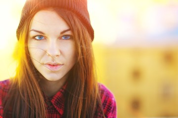 Portrait of trendy beautiful long haired girl with blue eyes the hat in sun on a blurred background, closeup.