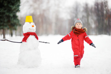 Kid during stroll in a snowy winter park