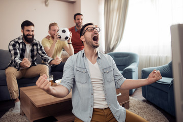 Group of friends watching football game together