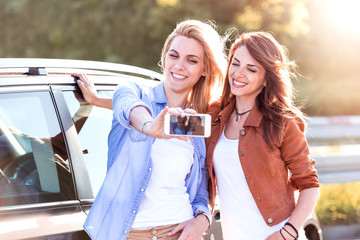 Smiling girls taking selfie with smart phone in the city