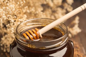 Buckwheat honey with dry flower background