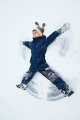 the boy lies on the snow in a winter overall, shows a snow angel