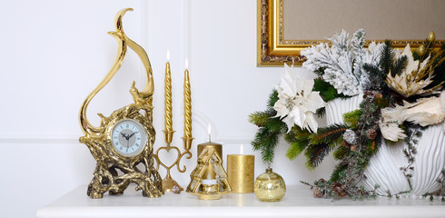 New Year and Christmas composition. Decorative golden clock, thick candles, candlestick, pot of flowers and framed canvas that hangs on the wall