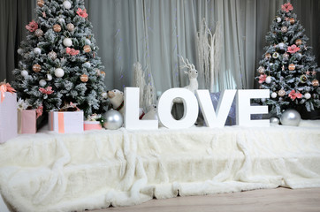 "New year cozy interior with a large plush veil, two Christmas trees, toy forest animals and the inscription ""love"" of big white letters"