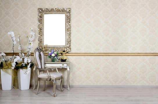 A fragment of a retro interior with a chair and table, on which is a telephone and a vase of flowers. Above the table hangs an empty picture frame for your photo