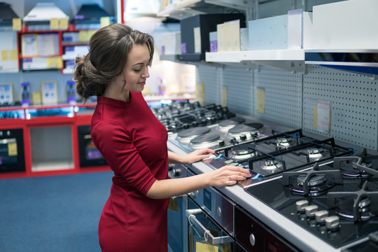 Smart modern female housewife customer choosing large gas stove and oven in domestic appliances section.