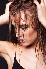 Woman with wet shining  makeup and closed eyes on black background