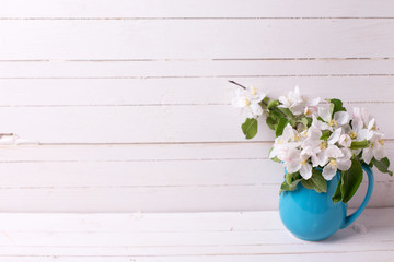 Tender apple tree flowers in blue pitcher  on white wooden background.