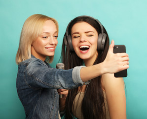lifestyle, emotion  and people concept: Happy girls  with microp