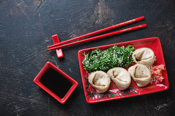Red tableware with steamed asian seafood dumplings, seaweed salad and soy sauce. Top view on a dark brown stone surface with space