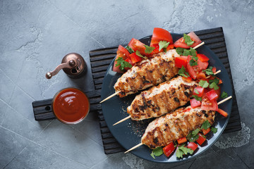 Plate with roasted chicken lula kebabs and fresh vegetables on a black wooden serving board. Top view on a gray concrete background