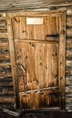 Old wooden door of a log house close-up.