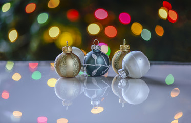 Colorful ornaments in front of tree lights