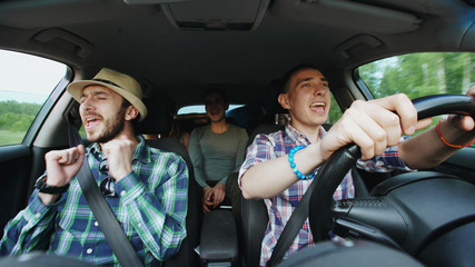Group of happy friends in car singing and dancing while drive road trip