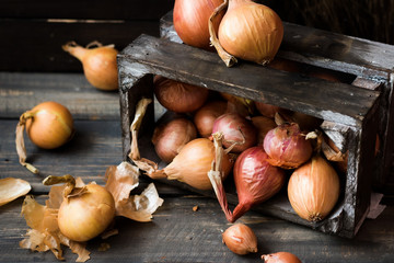 Onion in a wooden box on a dark background