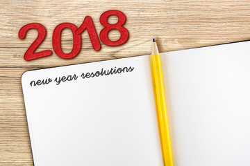 Top view of 2018 new year resolution with blank open notebook and yellow pencil on wooden table top,Mock up for adding your content or design.