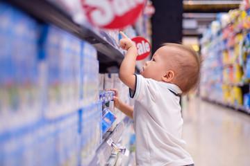 Asian Toddler boy choosing milk in grocery store