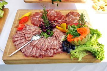 Wooden tray with salami. Buffet. Pancetta. Catering