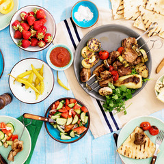 Dinner table with shish kebab, grilled vegetables, salad, snacks, strawberries