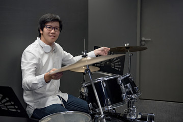 Young Asian man sitting with drum set in music practice room