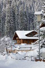 Fototapete - Snow-covered winter holiday house in mountains