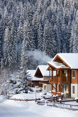 Fototapete - Snowy winter in mountains. Wooden cottage in Austrian Alps