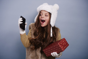 Excited girl with mobile phone and gift box