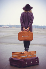 Vintage style, traveler elegance woman going with suitcases on the road over airport building in autumn or winter time. Concept of travel, holidays, journey, trip.