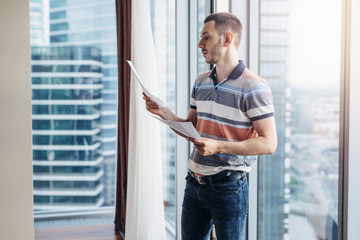 Businessman holding reading documents standing by the window in office
