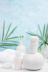 Spa background: thai massage bag, cosmetics, towels and palm leaves on blue background. Healthy lifestyle. Text space