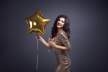 Woman holding champagne flute and balloon