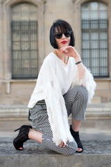 Woman with brunette hair, red lips in sunglasses in paris