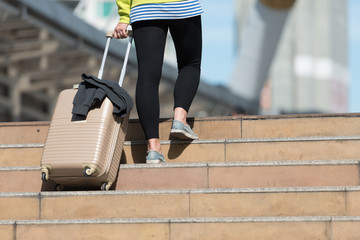 Back view of female tourist with suitcase while walking up staircase in city building, Travel concept