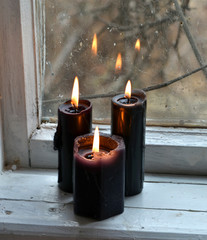 Burning black candles against the old window. Occult, esoteric, divination and wicca concept, mystic background