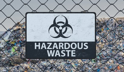 3D rendered illustration of hazardous waste sign on chain link fence. Landfill in background.