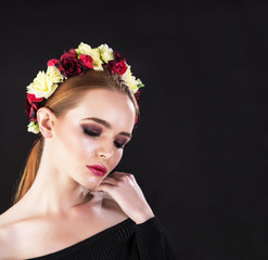 Gentle portrait of a ginger girl with professional makeup and crown made from roses on head