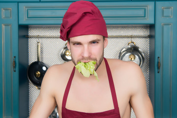 Guy hold salad leaf in mouth