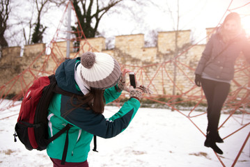 Girl with backpack makes a photo of another girl