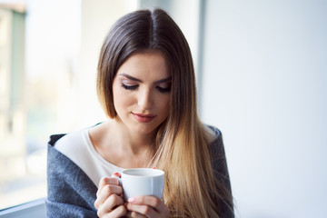 Calm young woman drinking coffee sitting cosily at home