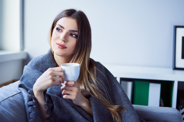 Young woman sitting under blanket on sofa having coffee and looking away