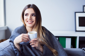 Cheerful young woman drinking coffee sitting under blanket on sofa at home