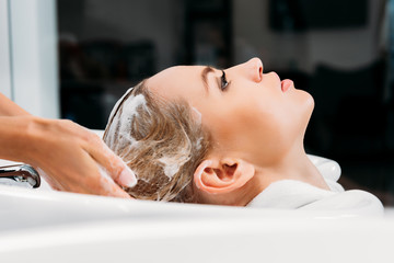 side view of hairdresser washing hair for customer with shampoo