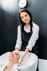 smiling hairdresser drying washed customer hair with towel and looking at camera