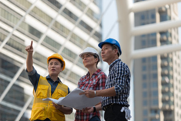 Asian engineers group consult construction on site building working while holding blueprint paper. in city background. teamwork concept.