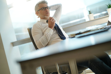 Businessman talking on phone in office, relaxing in chair