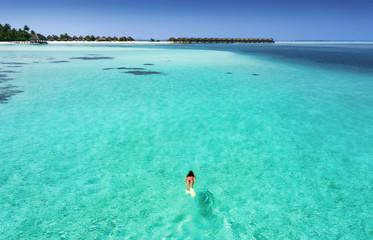 Frau im Bikini schnorchelt in den türkisen Gewässern der Malediven, Luftaufnahme
