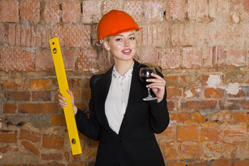 Beautiful blonde businesswoman with application tier at loft office in orange construction helmet and suit.
